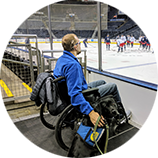man in wheelchair with Canine Companions service dog watching hockey game