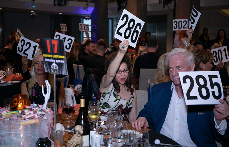 People sitting around tables holding bidding numbers up