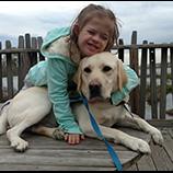 little girl hugging Canine Companions service dog