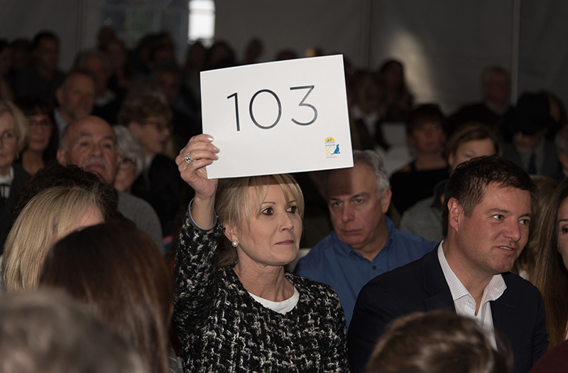 woman holding up a live aution bidding number with crowd around her