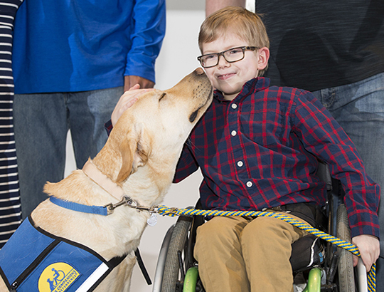 Man with prosthetic leg bending over to be nose to nose with yellow dog wearing a blue Canine Companions service dog vest.